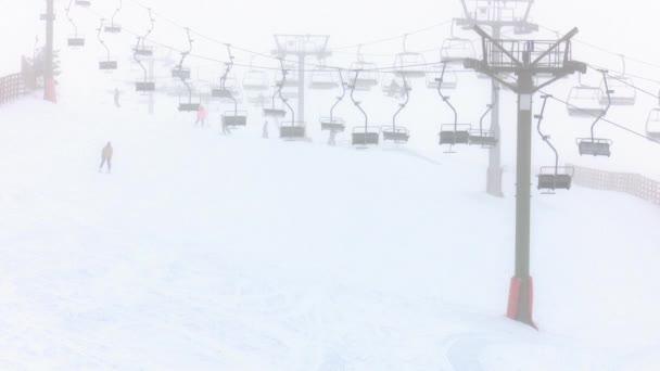 Ski- und Snowboardfahrer und ein Schneemobil überqueren die Strecke von rechts nach links, im Hintergrund Sessellifte und Menschen