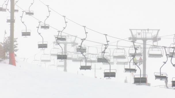 Sedačkové lanovky lyžařského střediska v provozu během sněhové bouře a mlhy a lidé užívající si snowboarding