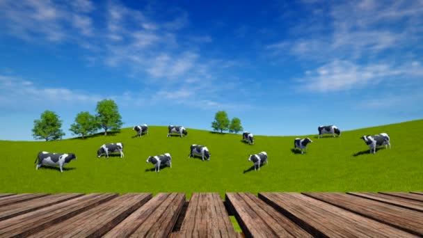 Perspektivy dřevo stůl a krávy se pasou na zelené louce