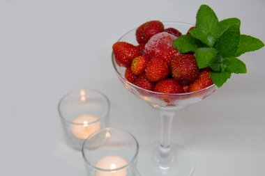 frozen strawberries with mint leaves in a glass and candles on a white background