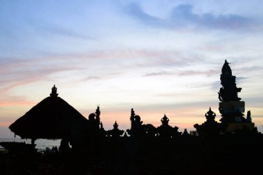 Tropical sunset with Indonesian temple silhouettes.