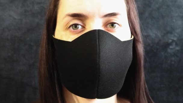 Coronavirus. Portrait of a girl with beautiful green eyes in a black medical mask on a gray background. Young woman looking at camera close-up. The epidemic concept of Covid-19. pandemic 2019-nCoV