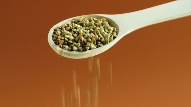 Nalévání zrnka zelené pohanky na hnědé pozadí s dřevěnou lžičkou. Syrová zdravá organická strava. Zdravá vegetariánská ekologie potravin. Dietní produkt. Koncept hubnutí. 4K jídlo video.