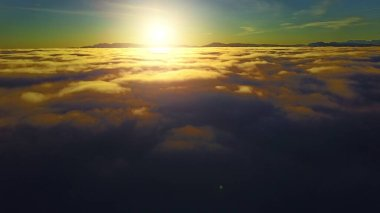 Flying through heavenly beautiful sunny cloudscape. Amazing timelapse of golden fluffy clouds moving softly on the sky and the sun shining through the clouds with beautiful rays and lens flare.