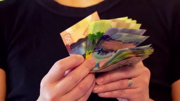 Woman counting Canadian currency bills with her hands