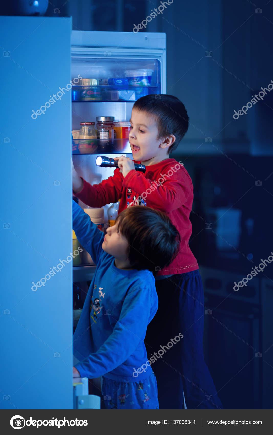 zwei kleine jungs heimlich essen s igkeiten aus dem k hlschrank in der nacht stockfoto t. Black Bedroom Furniture Sets. Home Design Ideas