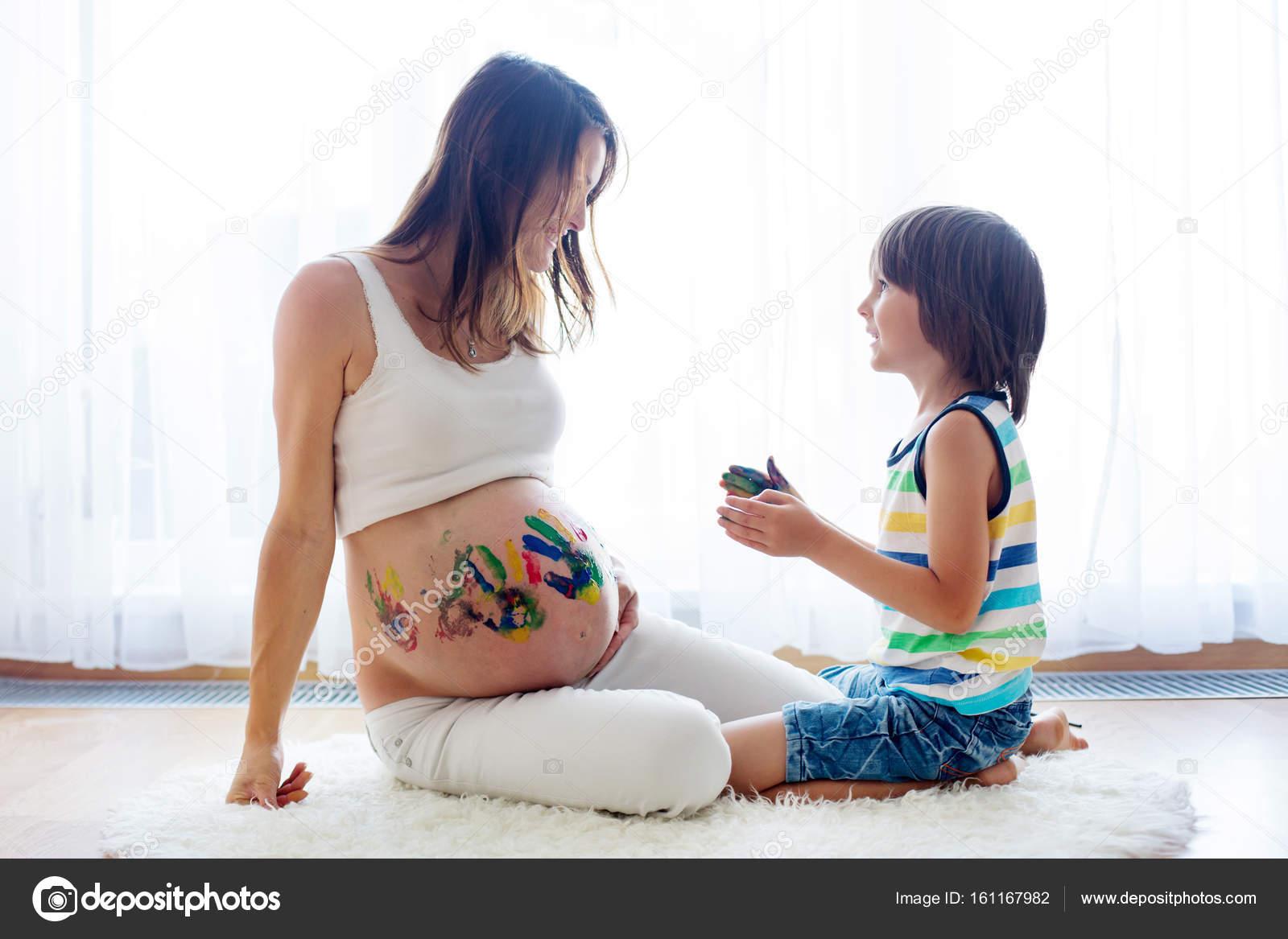 Gelukkig kind jongen schilderen op mama s zwangere buik