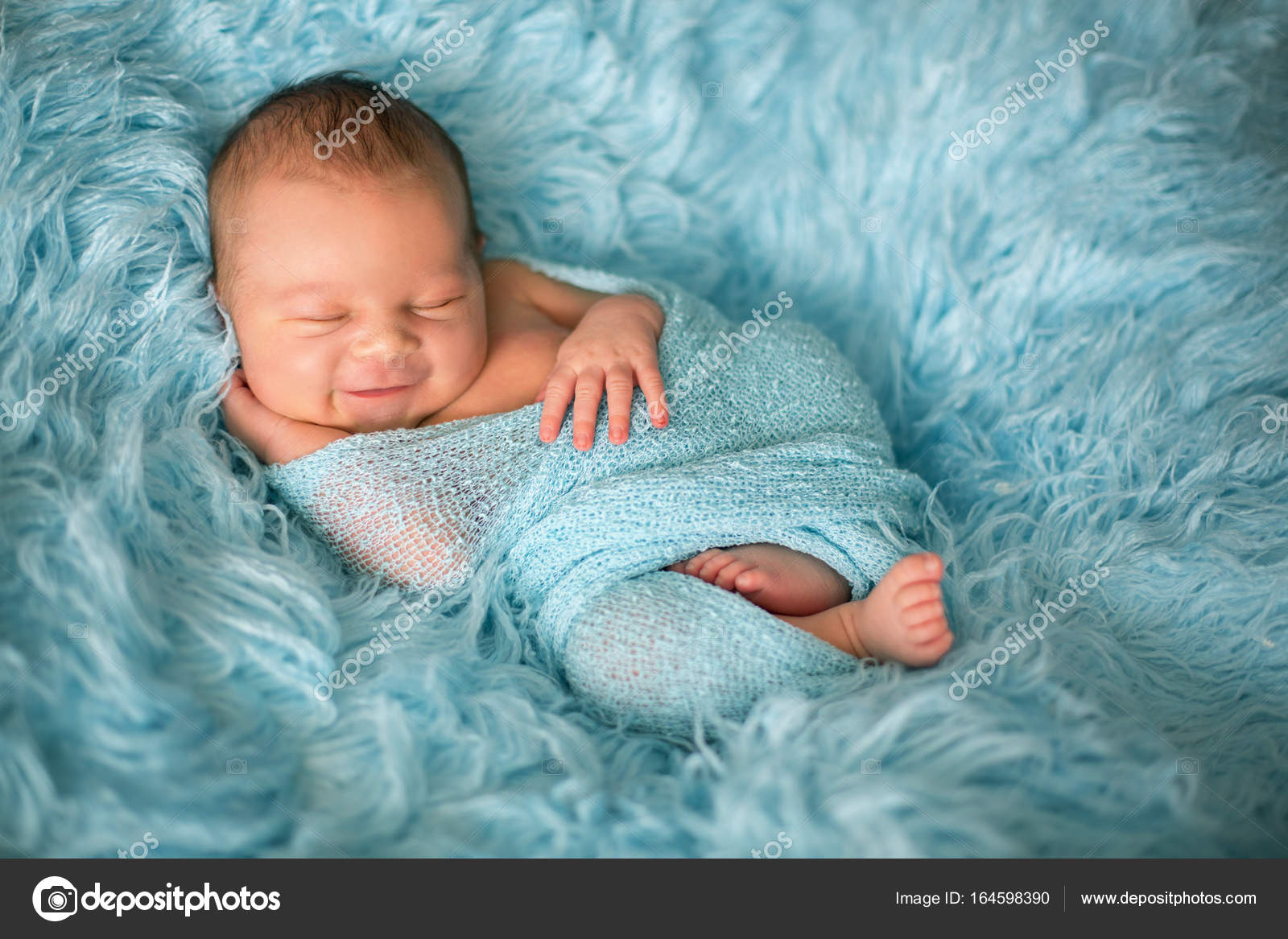 Happy Smiling Newborn Baby In Wrap Sleeping Happily In Cozy Fur