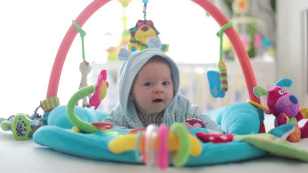 Cute baby boy on colorful gym playing with hanging toys at home