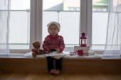 Édes szőke gyermek, fiú, ül az ablakon pajzs Teddy Bea