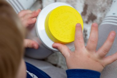 A child independently tries to open a plastic bottle of medicine
