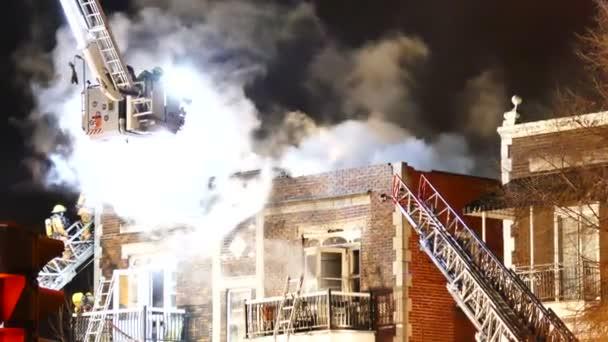Hasiči na high-tech zvýšené plošině dávat vodu na budování ohně