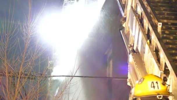 Voda stříkající na střeše domu v noci s hasičem a žebřík