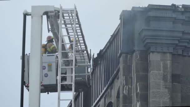 Feuerwehrmann zerreißt in Flammen stehende Gebäudeteile