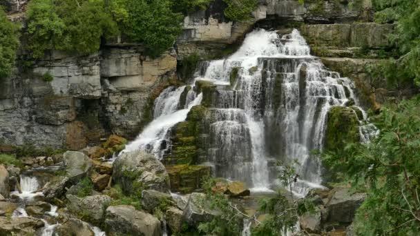 Krásný vodopád v bujné zelené vegetace nastavení s tekoucí vodou