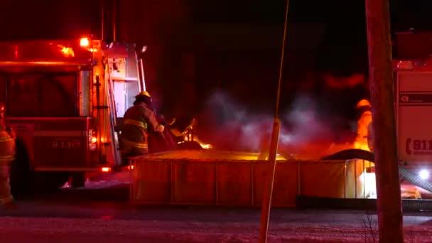 Hasiči pracující na venkově požár pomocí nafukovací přenosné nádrže na vodu