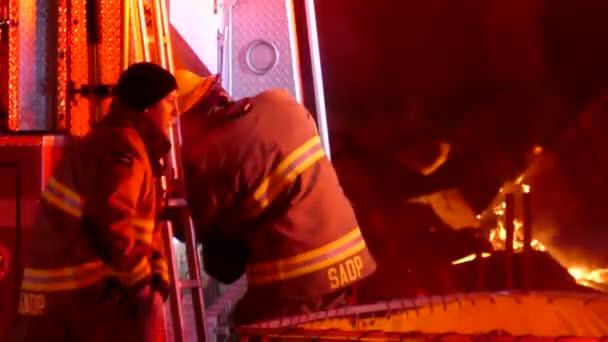 Hasiči pracují na zadní části hasičského vozu cisterny, zatímco požár hoří za
