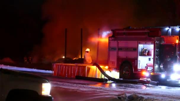 Hasiči pracují na místě požární nádrže, zatímco jeho kolegové bojují za
