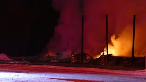 Hasiči dokončují hašení požáru stodoly za osvětlenou venkovskou silnicí v zimě