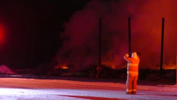 Červená blikající hasičské auto zálohování s pomocí hasiče na místě požáru