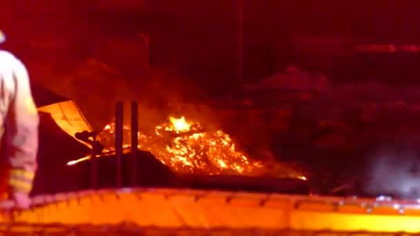 Hromada zuhelnatělých trosek hořících v oranžové záři v dálce s hasičem před námi