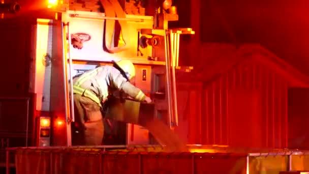 Hasič kapající vodu z hasičského vozu zařízení do zásobníku tankeru naplnit hadice