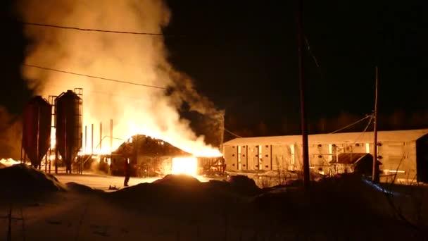 Obří požár v plném rozsahu zahrnující velkou stavbu na farmě v Kanadě během zimy