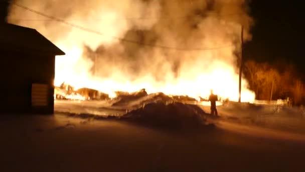 Těžké plameny vypalující zřícenou budovu a trosky během požáru