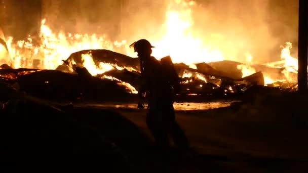Silueta hasiče kráčejícího po malém zasněženém kopci se zuřícím peklem za zády