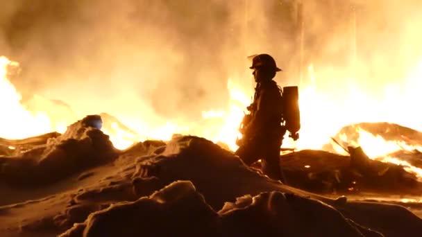Přiblížení záběru hasiče čekajícího na zásoby, zatímco hoří těžké plameny