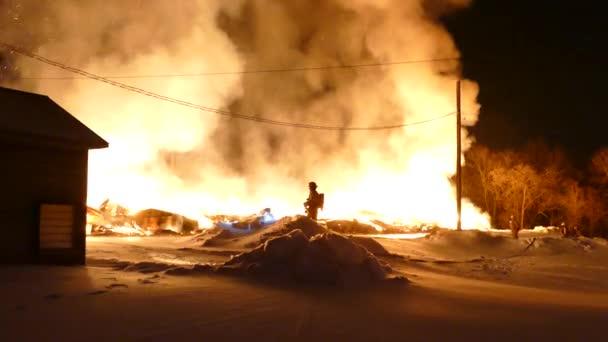 Masivní peklo hoří, zatímco jediný hasič stojí na malé sněhové hromadě