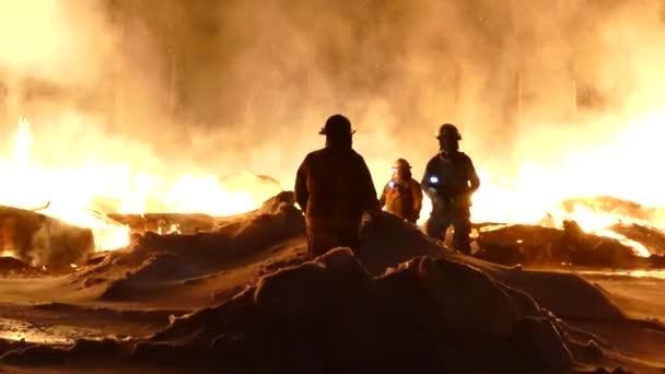 Malá skupinka hasičů mluví v popředí jasně trhajících plamenů