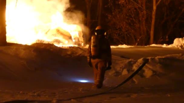 Vyčerpaný hasič odcházející v hlubokém sněhu s plameny hořícími poblíž