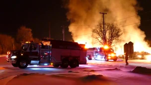 Hasič vede hasičský vůz na místo na scéně obrovského požáru v zimě