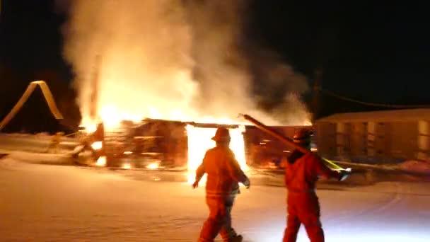 Hasič a údržbář chůze, zatímco velká budova hoří v pozadí