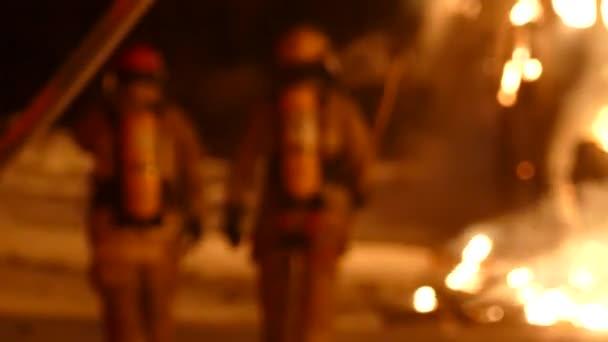 Pohled zezadu na dva hasiče odcházející podél hořících zdí budovy