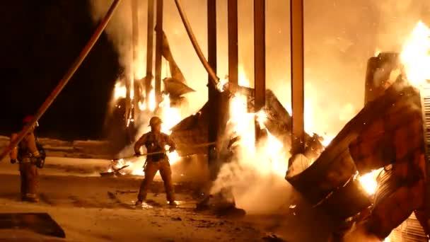 Dramatický záběr hasiče, který se snaží během masivního požáru pohnout hořící zdí