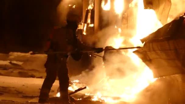 Úžasný posloupnost hasičů tahání na kovovou stěnu v plamenech s bodcem nástroj