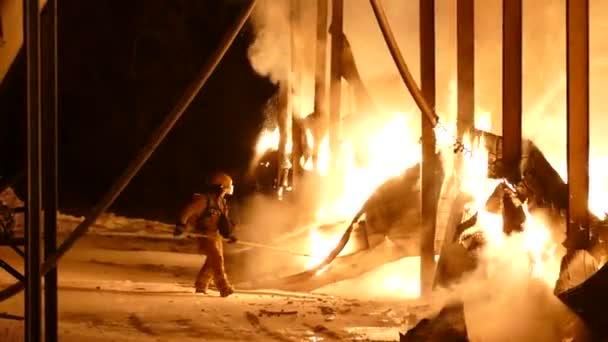 Ohromující pohled na požárníka čelícího velkému požáru na venkovské farmě