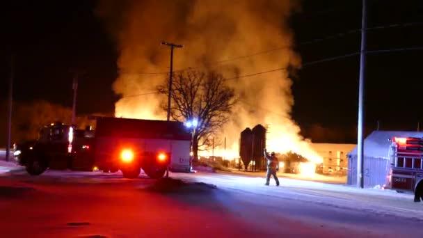 Hasič pomáhá hasičský vůz řidiče zálohovat s velkým požárem a plameny za