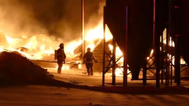 Zemědělské struktury hořet ve venkovské kanadské nastavení zobrazující dva hasiči