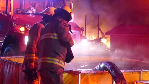 Tři hasiči hledající současně do přenosné nádrže na vodu během požáru