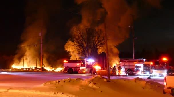 Působivá zimní požární scéna se dvěma hasičskými vozy zaparkovanými v popředí