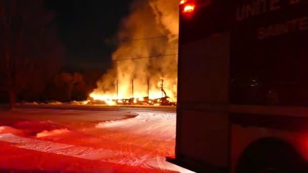 Kameraman kráčí za hasičským vozem, jen aby pak odhalil pohled na velký požár