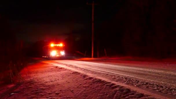 Pan záběr hasičského vozu na venkovské silnici přijíždějící k velkému požáru farmy ve venkovském prostředí