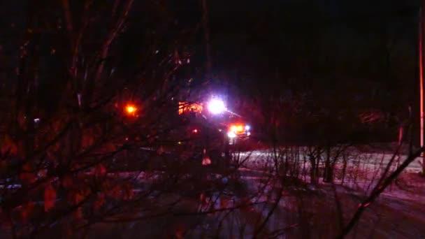 Fire Truck s červenými blikajícími světly přijíždějící na scénu obrovského požáru budovy