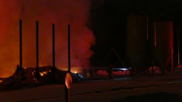 Temná zima chladná noc na požární scéně zahrnující dva hasiči v aktivní bitvě