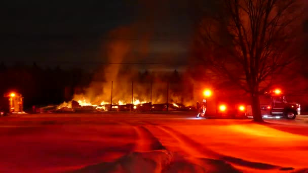 Hasič šlápnutí na zadní straně hasičského vozu, zatímco velmi velký oheň hoří v pozadí