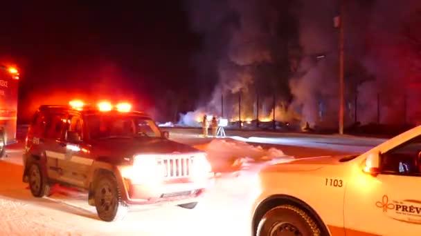 Pohotovostní osobní vozidla zaparkovaná s blikajícími stroboskopickými světly na místě požáru