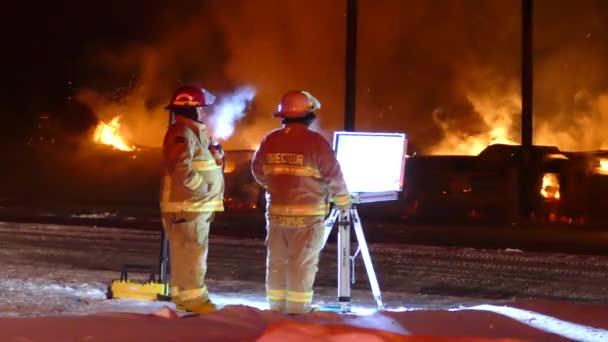 Dvojice hasičů stojící na velitelském stanovišti s plameny hořícími v pozadí